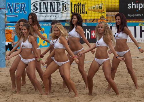 Team of Hot Volleyball Cheerleaders Dancing on the Sand in Revealing White Bikinis