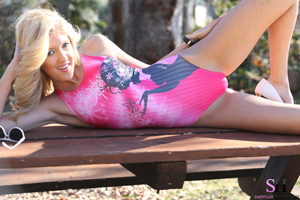 Blonde Emily teases in a pink swimsuit