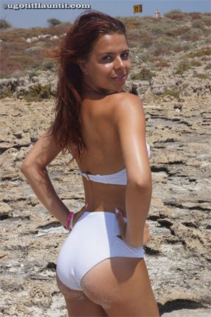 Liz is posing in her white bikini for UGotItFlauntIt on the beach in Ayia Napa