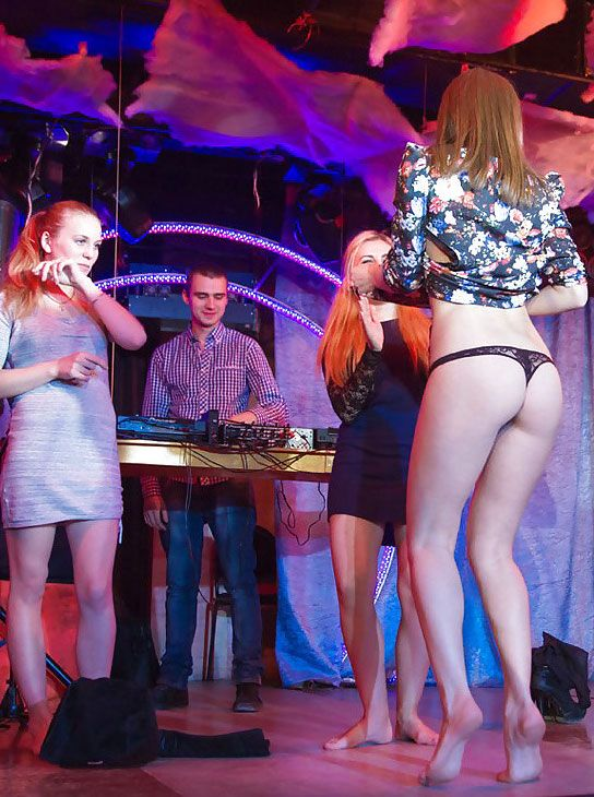 Cute girl lifts up her skirt on stage to show off her ass and panties
