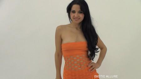 Hannah is posing in a cute orange dress