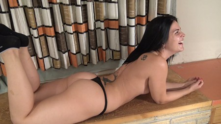 Maria is lying down in a black thong