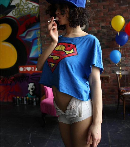 ShpitsyQ in a supergirl top on StasyQ, sucking on a lollipop