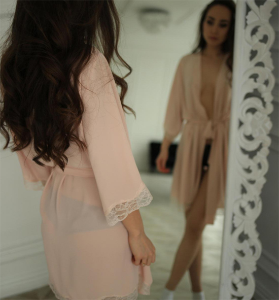 StasyQ brunette is looking at herself in the mirror