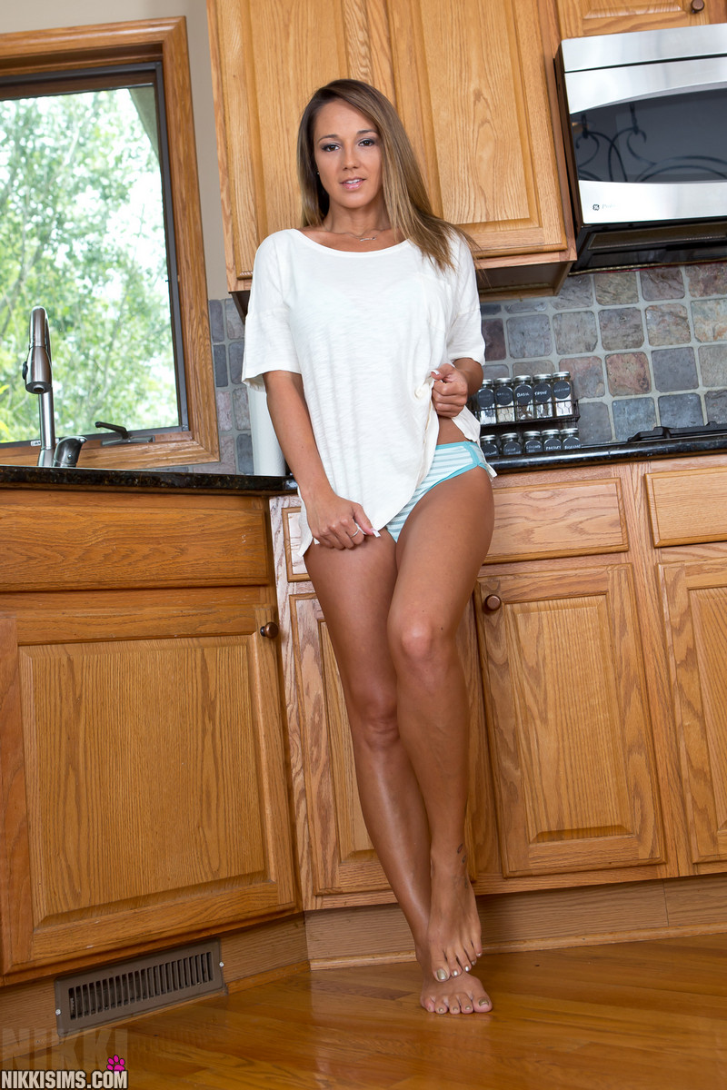 Nikki Sims in a white t-shirt in the kitchen