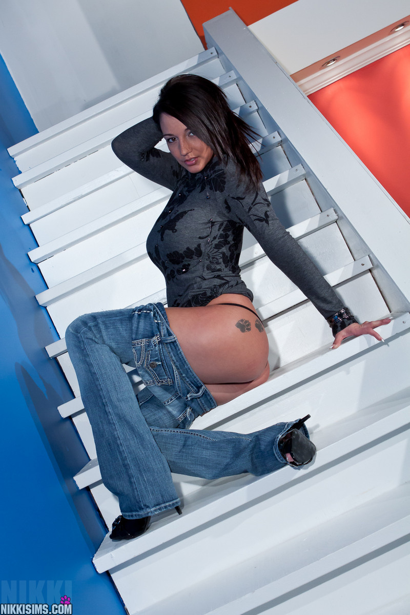 Nikki Sims sitting on the stairs with her jeans pulled down slightly