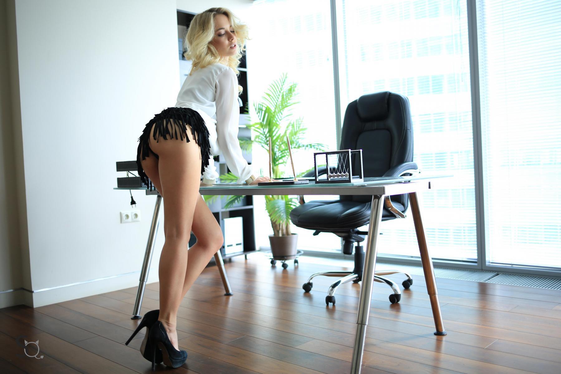 MonroQ leaning forward against her office desk-StasyQ