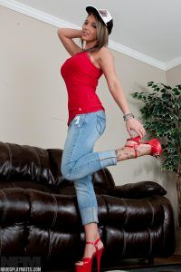 Posing in tight jeans, hight heels and a baseball cap