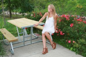 Meet Madden sitting at a picnic table in a white dress