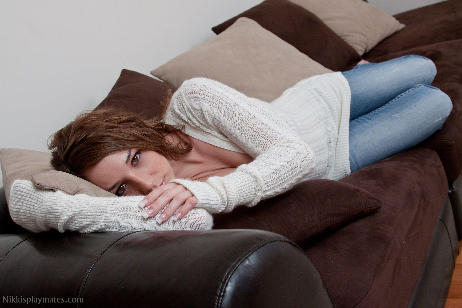 Nikki Sims relaxing on the sofa in jeans and white jumper
