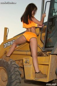 Clinbing onto a bulldozer Kari pushes out her sexy bum
