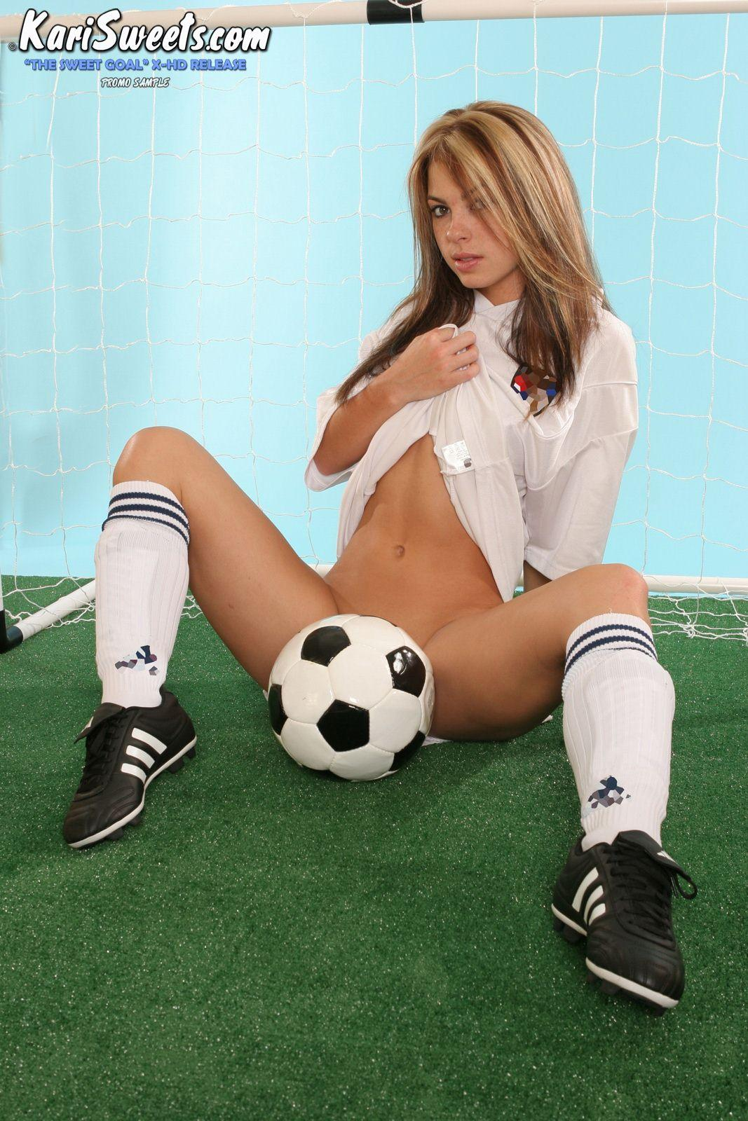 Hot bottomless girl spreads her legs and places a soccer ball between them