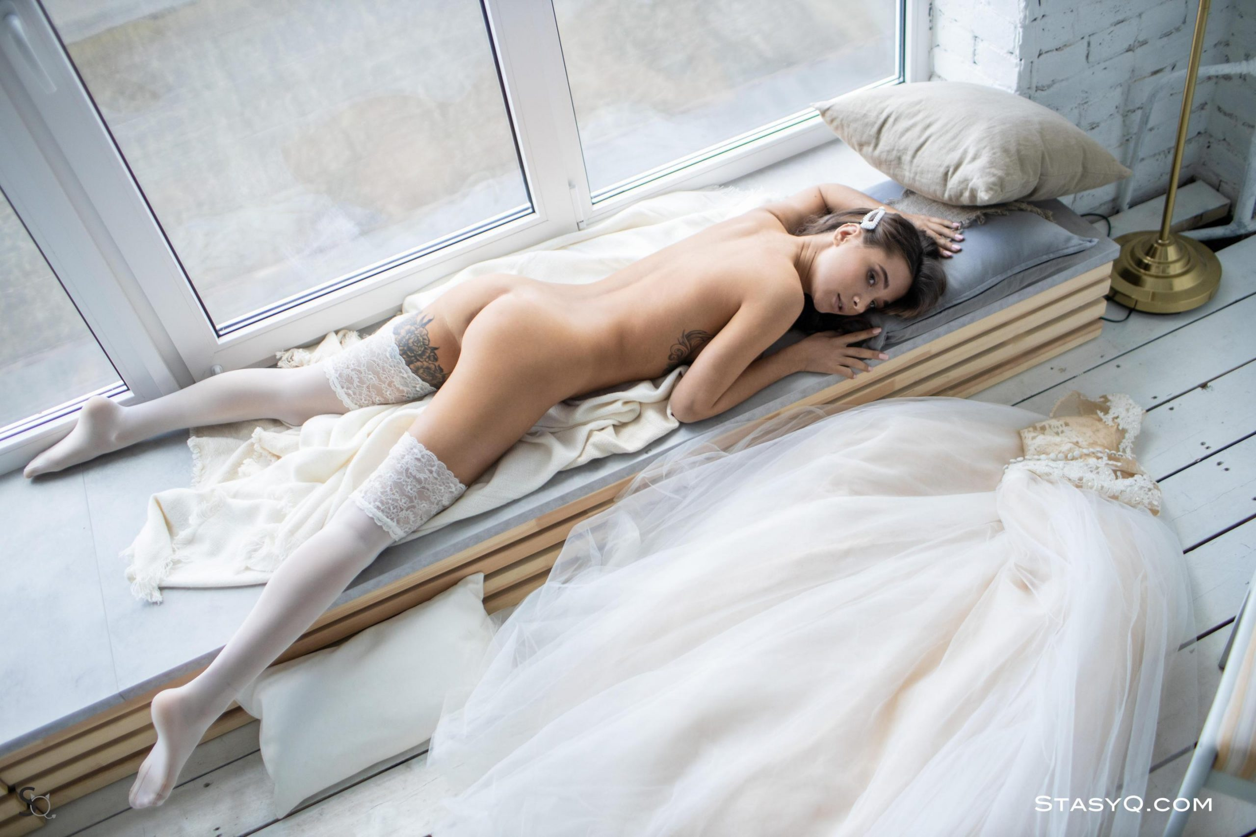 Sexy brunette lays naked by the window