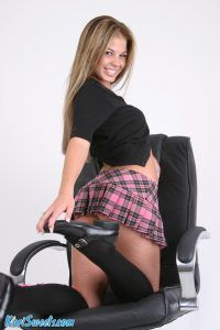She smiles as she shows off her plaid mini skirt
