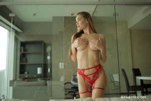 Naughty girl removes her bra and cups her firm breast with her hands in a handbra