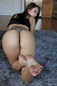 Now she kneels on the floor to show her juicy firm ass and bare feet