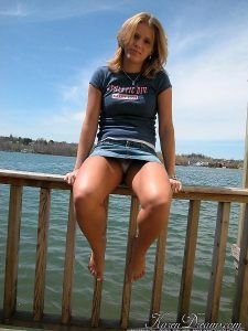 Karen Dreams shows upskirt while sitting on a wooden fence by the lake
