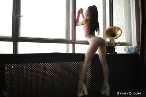 Horny lady shows off her sexy long legs by the window