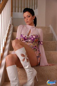 Sexy Karen Dreams sits on the stairs in her 60s mini dress and white flower power boots