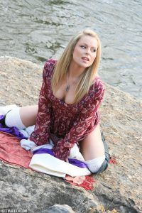 She sits by the lake and leans forward for a nice downblouse shot