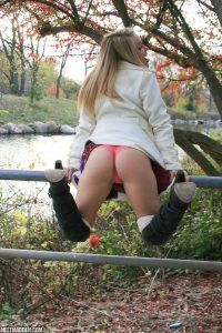 Gorgeous girl nextdoor bends over a metal fence for a beautiful view of her petite ass in pink panties