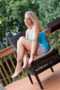 Nikki Sims sitting on her garden chair with a playful look on her face