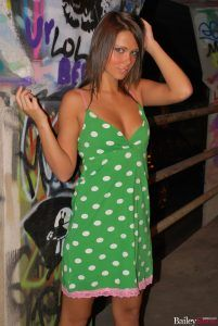 Bailey Knox looking sexy in her green dress surrounded by graffiti