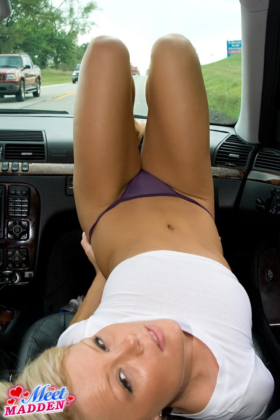 A blonde girl relaxes by putting her feet up on the dashboard of her car