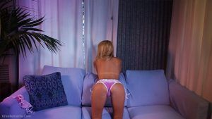 She bends over on the sofa for a wonderful view of her cute butt in purple panties