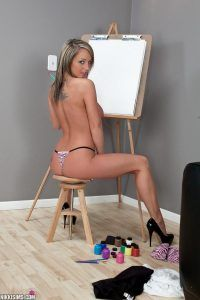 She sits on her stool and shows off her sexy body in a thong and high heels