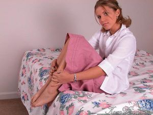 Shy looking Karen Dreams relaxes on the bed in her white blouse and long pink skirt