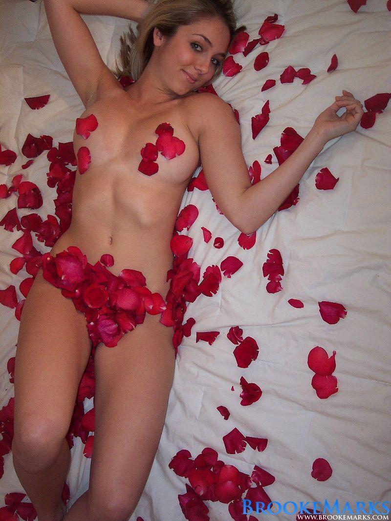 Loveable Brooke Marks laying on the bed surounded by red rose petals