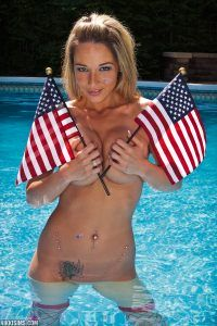 A blonde babe stands in the pool and holds her big boobs with two American flags