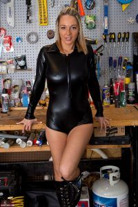 Nikki Sims standing in the garage in her sexy leather outfit