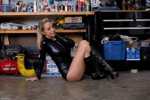 She sits on the floor in her leather outfit and sexy leather boots
