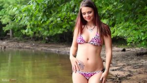 Brunette standing in the lake in her sexy bikini