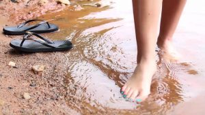She shows her bare feet as she paddles in the water