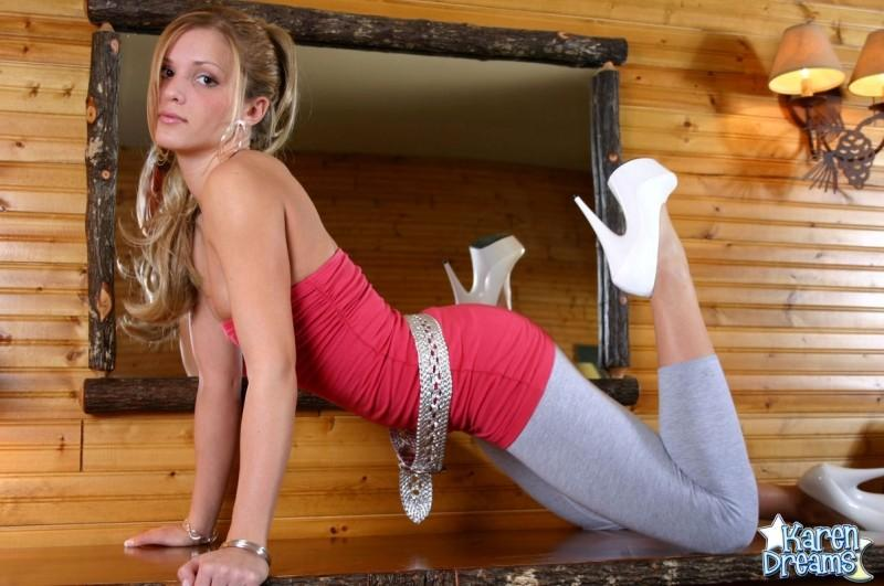 Blonde girl looking in to the camera as she bends over on a chest of drawers