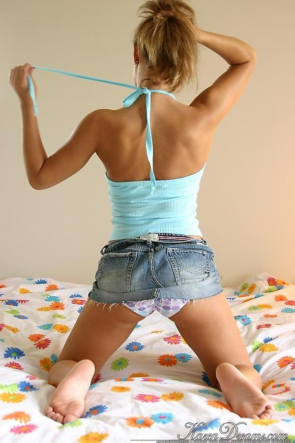 Karen Dreams kneeling on the bed with her denim skirt pulled up for a sneaky view of her panties