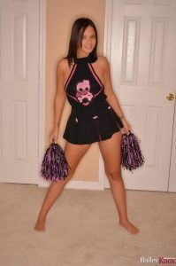 Brunette Bailey poses as a sexy cheerleader