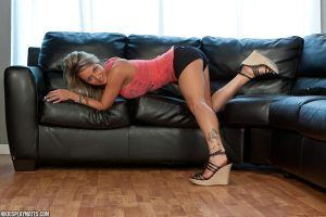 She's bending over on the black leather sofa with a cheeky smile on her face