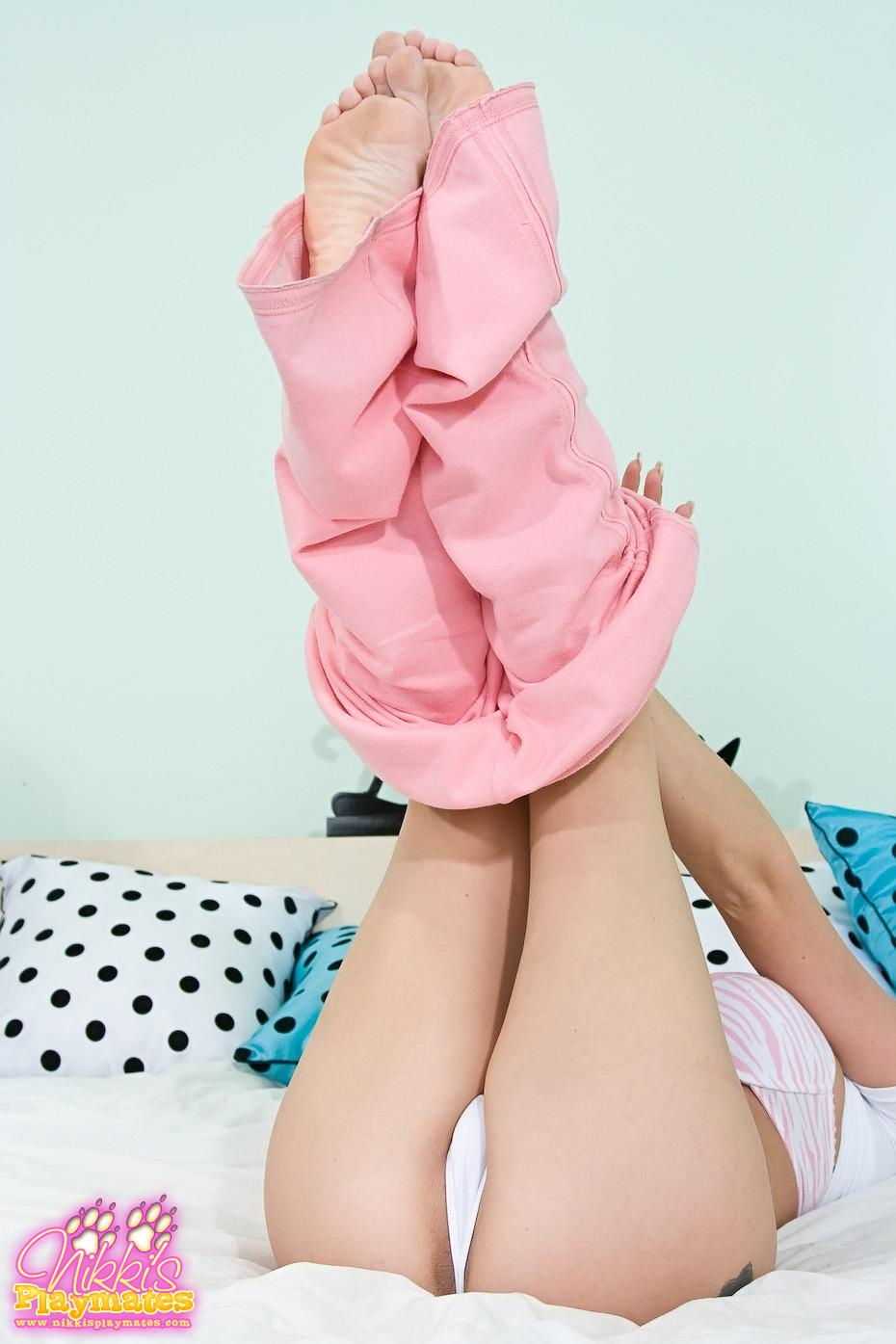 She's lifting her legs up to remove her pink tracksuit bottoms
