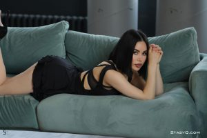 Brunette AiculQ relaxing on her sofa in her sexy black dress for StasyQ