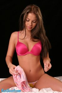 Kari Sweets is removing her top to show her sexy pink bra