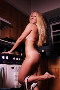 Beautiful blonde Brooke looking over her shoulder and smiling as she stands naked in her kitchen