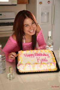 Smiling Kari Sweets posing next to her lovely looking birthday cake