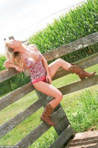 Madden is sitting on a wooden fence as she touches her pink panties