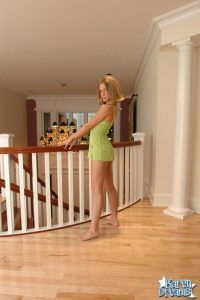 She's looking over her shoulder as she stands on top of the stairs in her sexy green lingerie