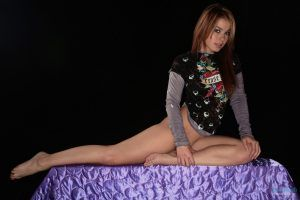 Kari Sweets sitting on a table in her tease me t-shirt and sexy thong