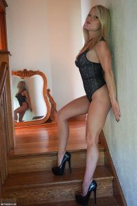 She's standing on the stairs in her black lingerie with her sexy reflection in the mirror behind her